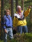 Farförälder med barnbarn i skogen